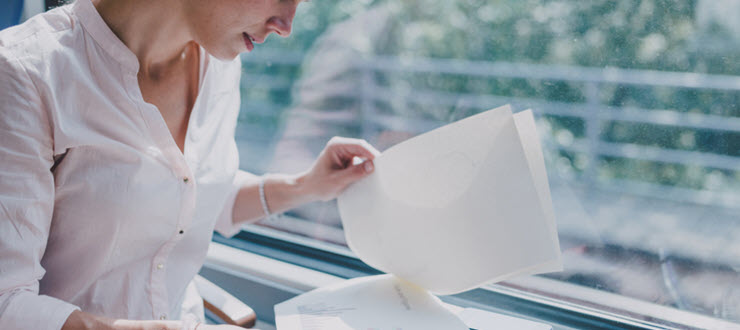 woman looking through application paper in front of window