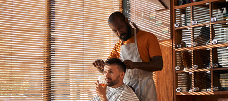 Man getting haircut by barber with liquor drink in hand