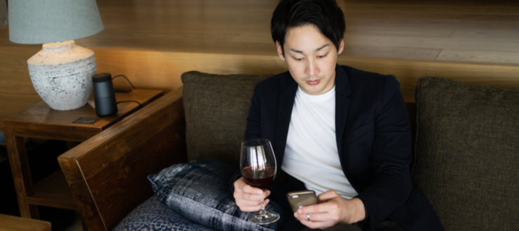 Man holding glass of wine in a hotel lobby