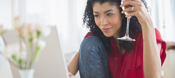 Woman with wine glass taste testing in front of laptop